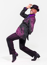 black comedian in purple jacket