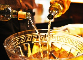 bottles being poured into punch bowl