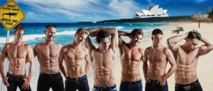 lineup of male strippers on beach
