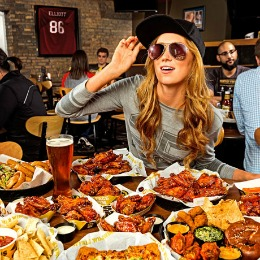 girl in sunglasses eating chicken wings