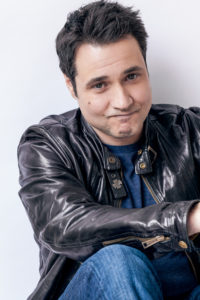 comedian in black leather jacket