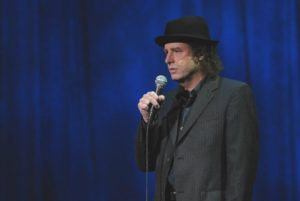 comedian in black hat
