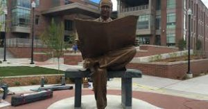 statue of man reading newpaper