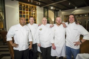 five chefs in white shirts