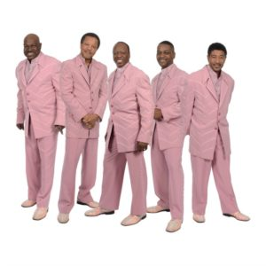 five singers in pink suits